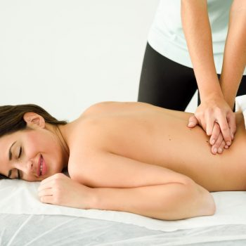 Young female receiving a relaxing back massage in a spa center. Brunette woman patient is receiving treatment by professional therapist.